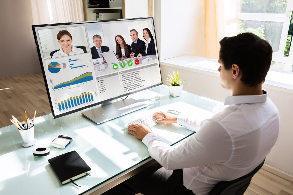 Young businessman videoconferencing with his partners on computer